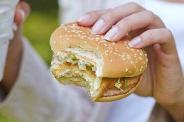 woman eating hamburger and cocktail